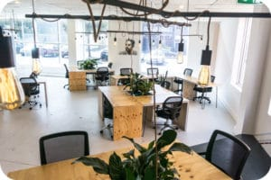 A co-working space with many empty desks and desk chairs
