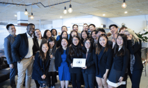 A group of international interns smiling and holding an award.