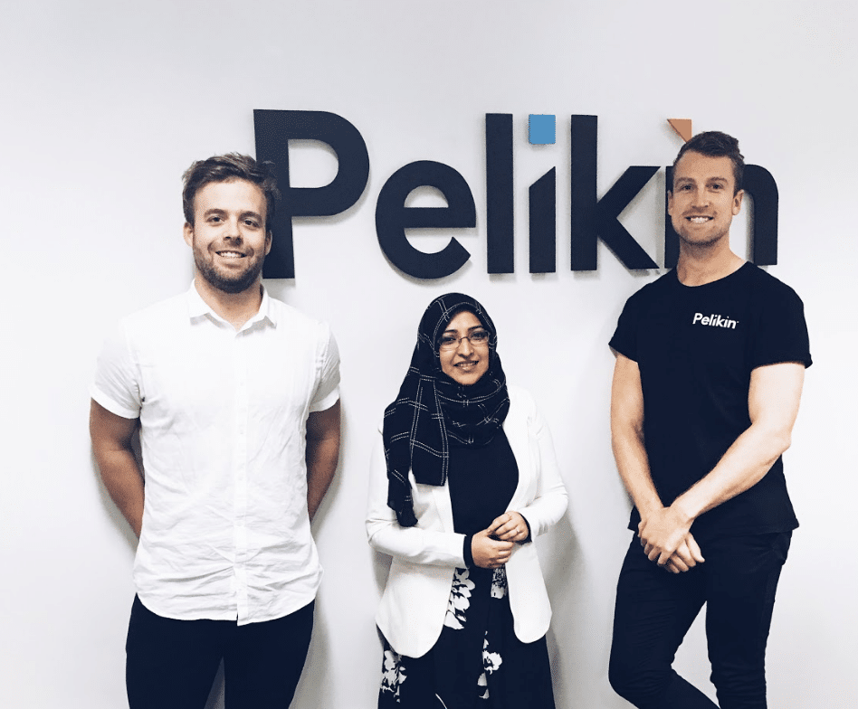 A female international student wearing hijab standing with two male internship host company mentors