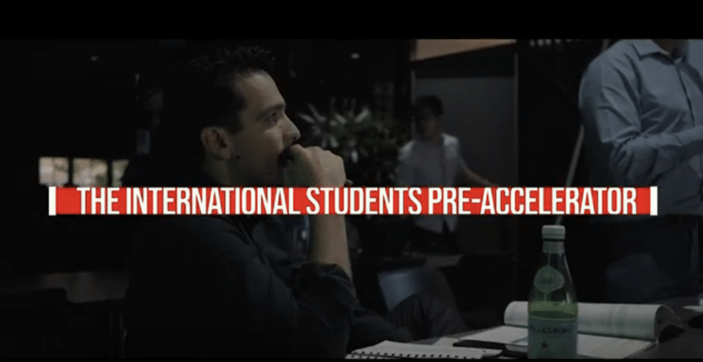 Students watching a presentation with text that says The International Students Pre-Accelerator in front of the image