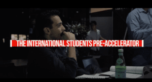 An international student sitting at a desk, watching a presentation with the text The International Students Pre-Accelerator overlaid across