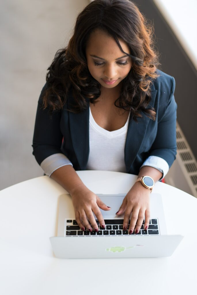 Woman types at her laptop in a business suit.