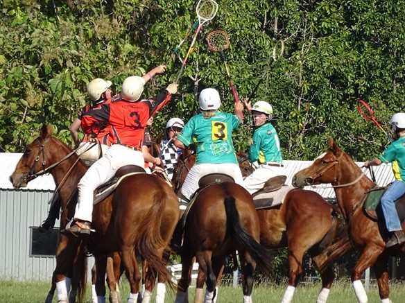 A group of women riding horses and playing polocrosse.