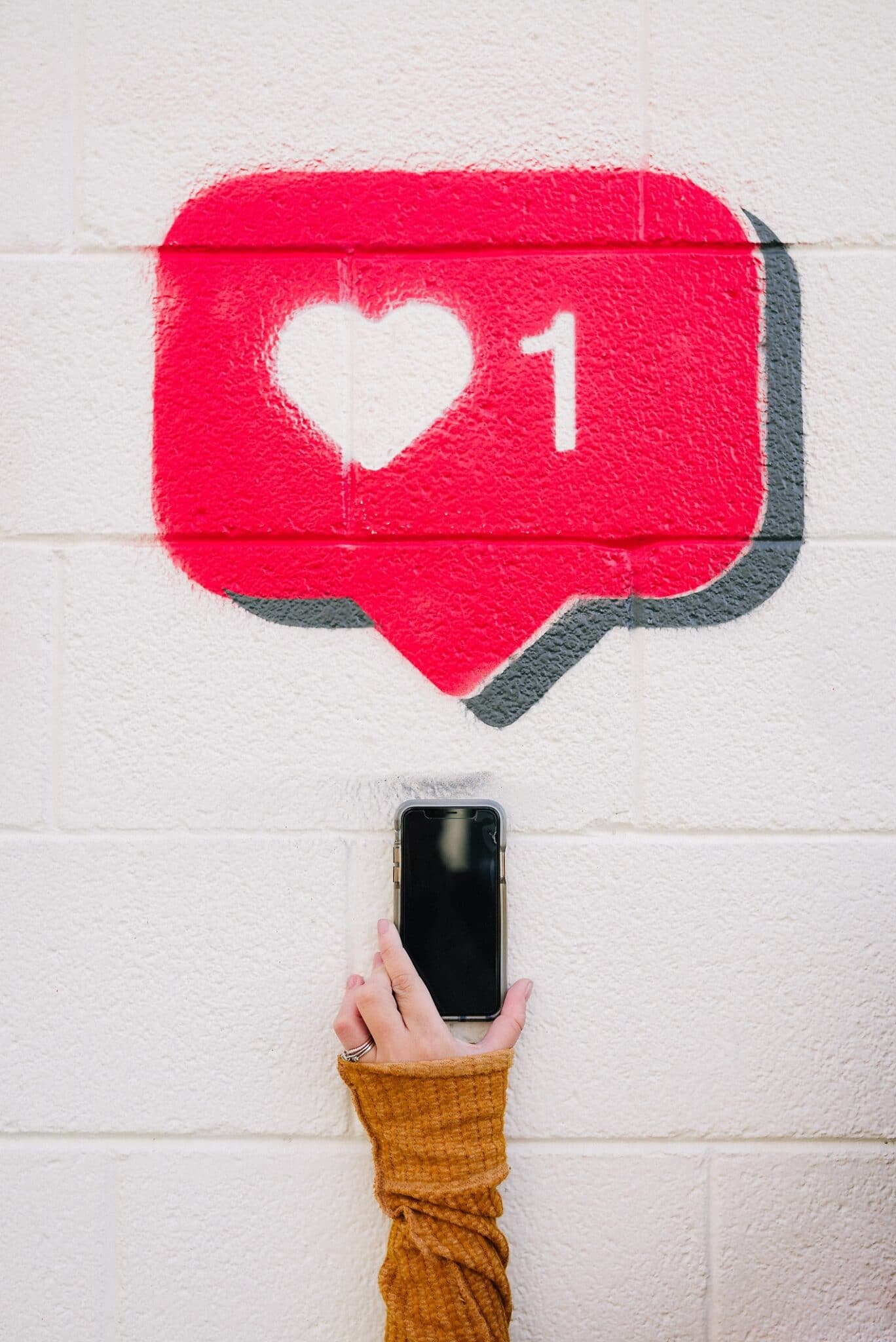 A smartphone with street art Instagram heart above it.
