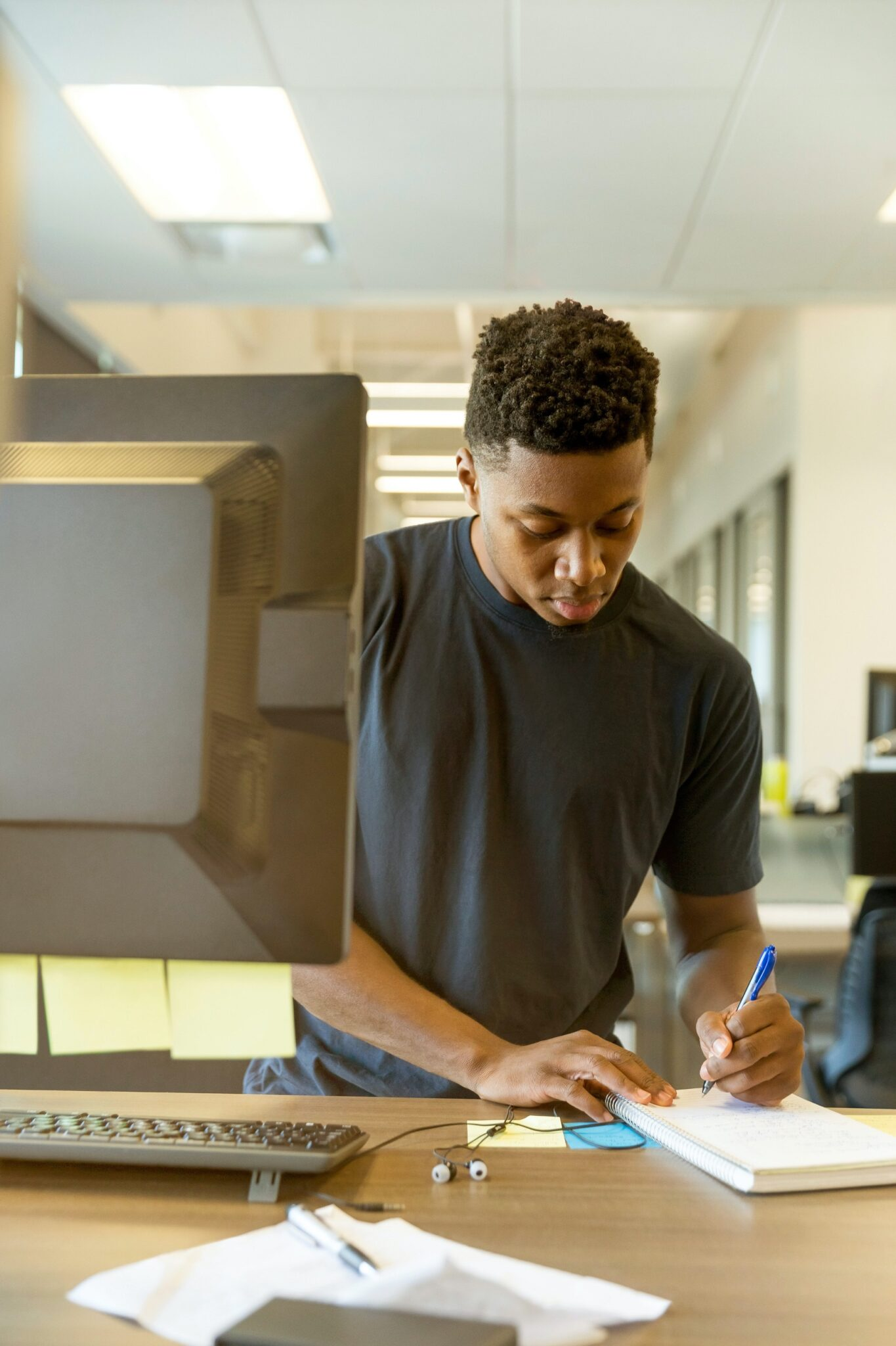 Intern working at a standing desk in front of his computer, writing in a notebook.