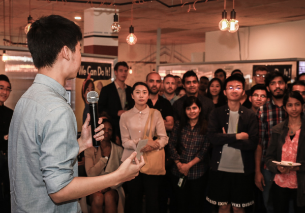 A man giving a speech to a group of international students
