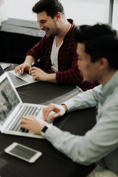 Two students on their laptops in a co-working space.