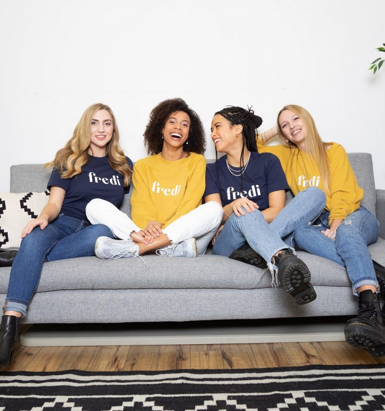Four professional women smile together on a couch.